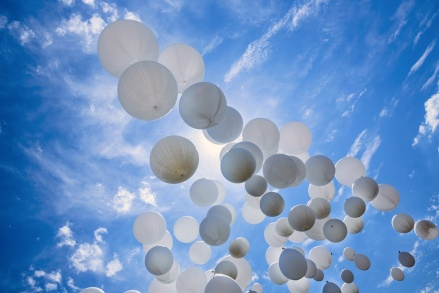 Many white balloons and celebration concept against the blue sky and clouds