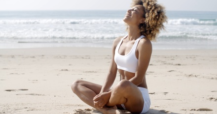 Portrait of a young woman sitting in yoga pose at the beach